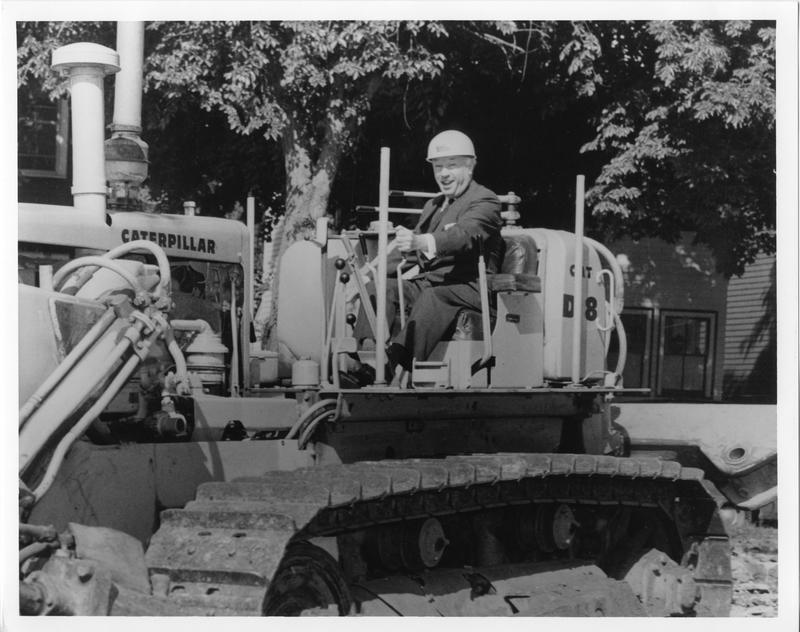 Photograph of President Henry Hicks on a bulldozer