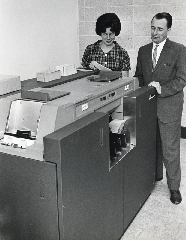 Photograph of Judy Hunter and an unidentified man with the Dalhousie computer in the Sir James Dunn Science Building