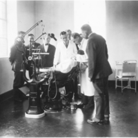 Photograph of men observing a dental examination in the public health clinic