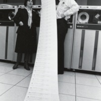 Photograph of Paula McNeill and John Pallas with long paper print-out