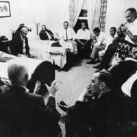 Photograph of a meeting taking place in a bedroom in Africville