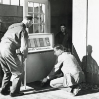 Photograph of men moving computer equipment into the Sir James Dunn Science Building