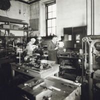 Photograph of two men working in a shop in the Science Building