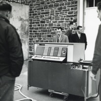 Photograph of men standing around computer equipment outside the Sir James Dunn Science Building