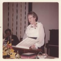Photograph of Electa MacLennan looking at a book